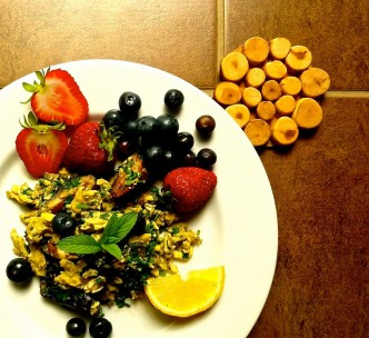 Scrambled eggs with mushrooms, parsley and fruits